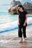 Jonge aantrekkelijke vrouw die op een zonnig strand bij kust lopen Reiziger en blogger royalty-vrije stock foto