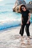 Jonge aantrekkelijke vrouw die op een zonnig strand bij kust lopen Reiziger en blogger stock fotografie