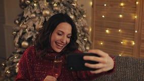 Jonge aantrekkelijke vrouw die selfie foto met mousserende wijn op Kerstmis binnenlandse achtergrond maken Het vieren van Nieuwja stock video