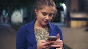 Jonge aantrekkelijke vrouw die slimme telefoon met behulp van bij nacht in stad Het mooie meisje texting op smartphone in openluc stock footage