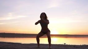 Jonge aantrekkelijke vrouw die sportoefeningen in de ochtend op zonsopgangstrand doen door overzees of meer Het doen zit UPS in s stock video