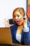 Jonge aantrekkelijke vrouw die van de bureaukleren en hoofdtelefoon zitting dragen door bureau die het computerscherm bekijken, v Stock Afbeelding