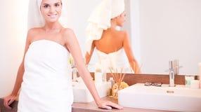 Jonge aantrekkelijke vrouw die zich voor badkamersspiegel bevinden Stock Foto