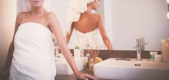 Jonge aantrekkelijke vrouw die zich voor badkamersspiegel bevinden Royalty-vrije Stock Fotografie