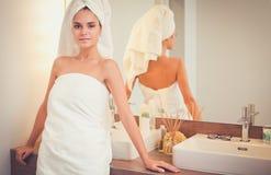 Jonge aantrekkelijke vrouw die zich voor badkamersspiegel bevinden Royalty-vrije Stock Foto