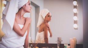 Jonge aantrekkelijke vrouw die zich voor badkamersspiegel bevinden Royalty-vrije Stock Afbeeldingen