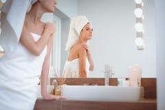 Jonge aantrekkelijke vrouw die zich voor badkamersspiegel bevinden Stock Foto's