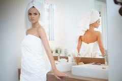 Jonge aantrekkelijke vrouw die zich voor badkamersspiegel bevinden Royalty-vrije Stock Afbeelding