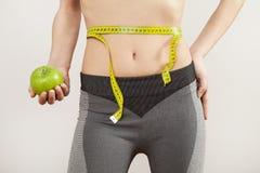 Jonge aantrekkelijke vrouw haar lichaam met maatregel op grijze achtergrond stock foto's