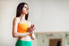 Jonge aantrekkelijke vrouw het praktizeren yoga, die namaste gebaar, het uitwerken maken, die sportkleding, oranje mouwloos onder Royalty-vrije Stock Fotografie