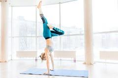 Jonge aantrekkelijke vrouw het praktizeren yoga die sportkleding, groene broek, grijze bustehouder, binnen volledige lengte drage Royalty-vrije Stock Afbeelding