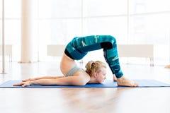 Jonge aantrekkelijke vrouw het praktizeren yoga die sportkleding, groene broek, grijze bustehouder, binnen volledige lengte drage Royalty-vrije Stock Foto