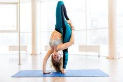 Jonge aantrekkelijke vrouw het praktizeren yoga die sportkleding, groene broek, grijze bustehouder, binnen volledige lengte drage Stock Foto's