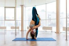 Jonge aantrekkelijke vrouw het praktizeren yoga die sportkleding, groene broek, grijze bustehouder, binnen volledige lengte drage Stock Fotografie