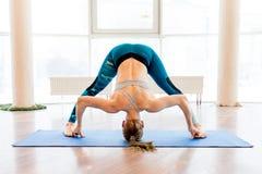 Jonge aantrekkelijke vrouw het praktizeren yoga die sportkleding, groene broek, grijze bustehouder, binnen volledige lengte drage Stock Foto
