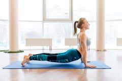Jonge aantrekkelijke vrouw het praktizeren yoga die sportkleding, groene broek, grijze bustehouder, binnen volledige lengte drage Royalty-vrije Stock Fotografie