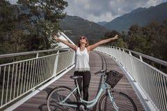 Jonge aantrekkelijke vrouw met fiets op een brug stock afbeelding
