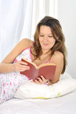 Jonge aantrekkelijke vrouw in nachtjapon liggen ontspannen op bed die nieuw boek lezen Stock Afbeeldingen