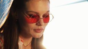 Jonge aantrekkelijke vrouw in rode zonnebril die tabletcomputer met touchscreen in een koffie met behulp van Mooi meisje in lucht stock footage