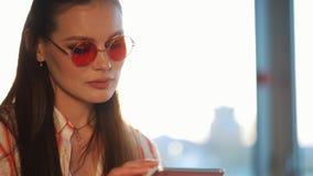 Jonge aantrekkelijke vrouw in rode zonnebril die tabletcomputer met touchscreen in een koffie met behulp van Mooi meisje in lucht stock video