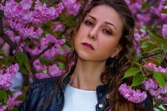 Jonge aantrekkelijke vrouw in roze bloemen in de tuin Meisje met krullend haar in witte kleding en zwart leerjasje openlucht stock foto's