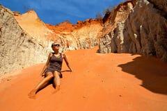 Jonge aantrekkelijke vrouw in zonnebril die in zandduinen zitten en hemel bekijken Royalty-vrije Stock Fotografie