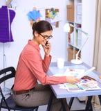 Jonge aantrekkelijke vrouwelijke manierontwerper die bij bureau werkt, dat terwijl het spreken op mobiel trekt Royalty-vrije Stock Afbeelding