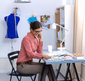 Jonge aantrekkelijke vrouwelijke manierontwerper die bij bureau werkt, dat terwijl het spreken op mobiel trekt Stock Afbeelding