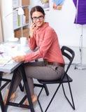 Jonge aantrekkelijke vrouwelijke manierontwerper die bij bureau werkt, dat terwijl het spreken op mobiel trekt Stock Afbeeldingen