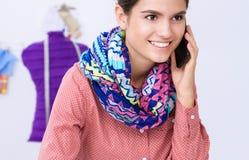 Jonge aantrekkelijke vrouwelijke manierontwerper die bij bureau werkt, dat terwijl het spreken op mobiel trekt Stock Foto