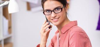 Jonge aantrekkelijke vrouwelijke manierontwerper die bij bureau werkt, dat terwijl het spreken op mobiel trekt Royalty-vrije Stock Afbeeldingen