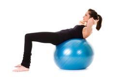 Jonge aantrekkelijke vrouwelijke oefening die bal gebruikt Stock Foto's