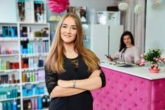 Jonge aantrekkelijke vrouwelijke receptionnist die van schoonheidssalon zich met gekruiste handen bevinden royalty-vrije stock afbeelding