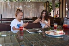 Jonge aantrekkelijke vrouwen die op slimme telefoons babbelen terwijl het zitten samen in modern restaurant tijdens middagpauze Royalty-vrije Stock Fotografie