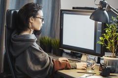 Jonge aantrekkelijke vrouwen freelancer ontwerper die aan PC thuis werken stock foto