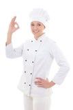 Jonge aantrekkelijke vrouwenchef-kok die o.k. teken toont dat op wit wordt geïsoleerd Stock Afbeelding
