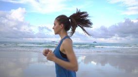 Jonge aantrekkelijke vrouwenjogging op het strand bij zonsondergang Mooie wolken, zonsondergang stock videobeelden