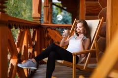 Jonge aantrekkelijke vrouwenzitting in openlucht op ligstoel met koffiekop en haverkoekje bij bergtoevlucht Wijfje  Stock Foto's