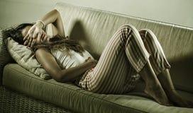 Jonge aantrekkelijke wanhopige en gedeprimeerde vrouw in pyjama's die periode aan pijn en de pijnlijke laag menses van de cyclus  royalty-vrije stock afbeeldingen