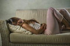 Jonge aantrekkelijke wanhopige en gedeprimeerde vrouw in pyjama's die periode aan pijn en de pijnlijke laag menses van de cyclus  stock foto