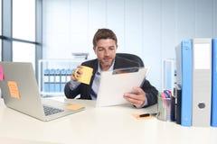 Jonge aantrekkelijke zakenman die gelukkige zeker werken op kantoor met laptop computer en administratie royalty-vrije stock foto's