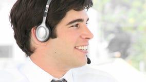 Jonge aantrekkelijke zakenman die op een hoofdtelefoon spreken stock videobeelden