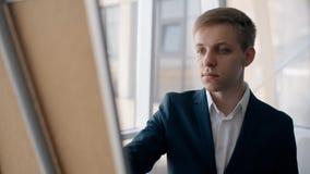 Jonge aantrekkelijke zakenman die op whiteboard tijdens werkdag in modern bureau schrijven stock videobeelden