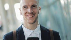 Jonge aantrekkelijke zakenman die zich dichtbij commercieel centrum met smartphone, koffie en hoofdtelefoons bevinden Hij onderzo stock videobeelden