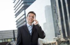 Jonge aantrekkelijke zakenman in kostuum en band die op mobiele in openlucht gelukkige telefoon spreken Stock Afbeeldingen