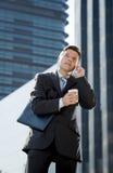Jonge aantrekkelijke zakenman in kostuum en band die op mobiele in openlucht gelukkige telefoon spreken Stock Fotografie