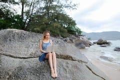 Jonge aardige vrouw die met laptop aan overzeese kust werken en op steen zitten royalty-vrije stock fotografie