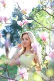 Jonge aardige vrouw die zich dichtbij magnolia in park bevinden Royalty-vrije Stock Foto