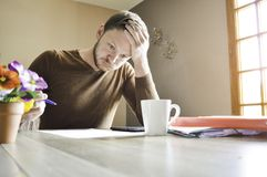 Jonge actieve mens zijn hoofd houden die hard werkend aan administratie bij het bureau stock foto