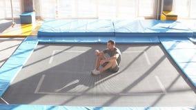 Jonge actieve sportman die op de vloer na de concurrentie rusten stock videobeelden